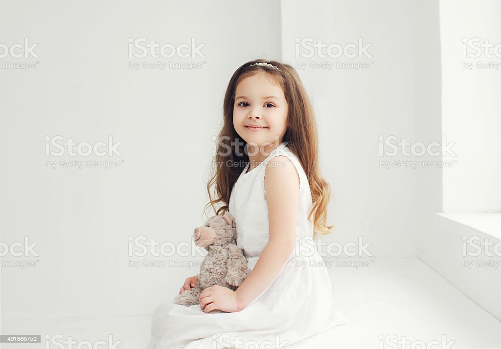 Beautiful little girl with teddy bear in white room stock photo