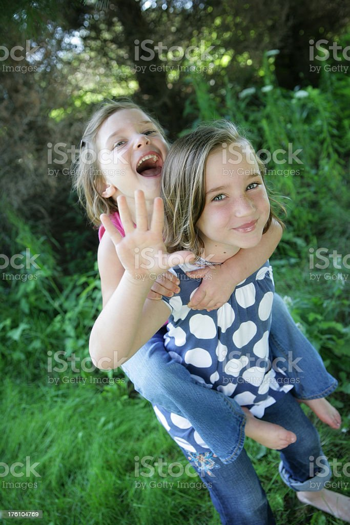 Beautiful Little Girls Smiling at Camera and Giving Piggyback Rides royalty-free stock photo