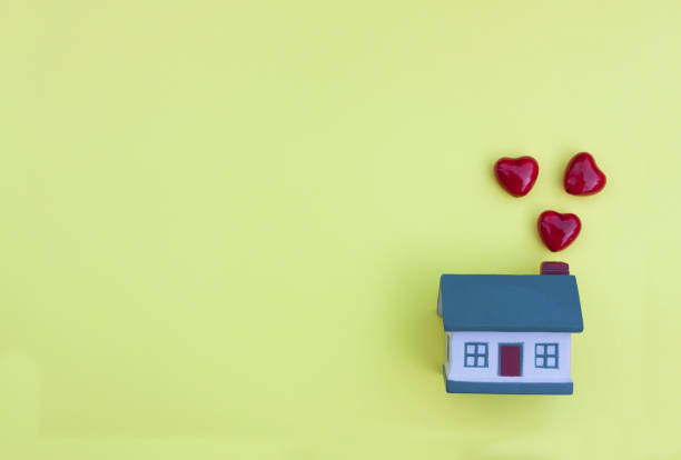 Beautiful little house, red hearts fly out of the pipe on a yellow background. The concept of happiness in your home, buying, selling, renting a property, mortgage stock photo