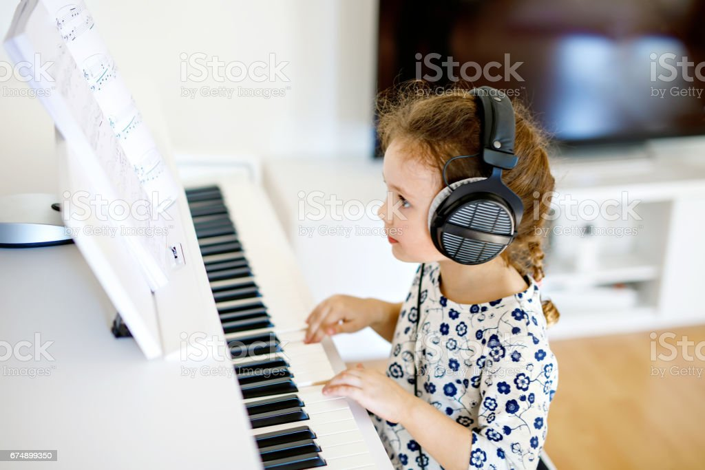 Beautiful little kid girl playing piano in living room or music school stock photo