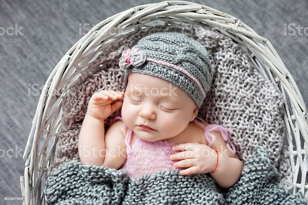 Beautiful little newborn girl 1 month sleeps in wattled basket. stock photo