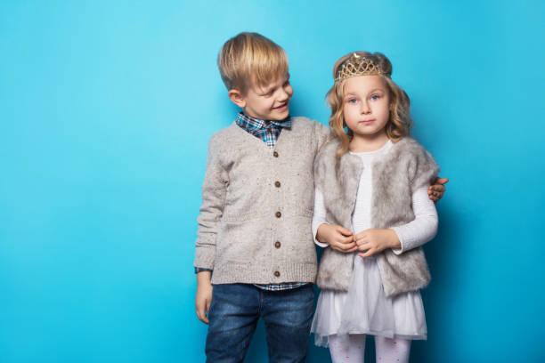schöne kleine prinzessin und hübscher junge. freundschaft. liebe. valentine. studio-porträt über blauem hintergrund - prinzessin kleid kind stock-fotos und bilder