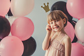 Cute little princess in dress is holding a crown, looking at camera and smiling, on gray background with colorful balloons