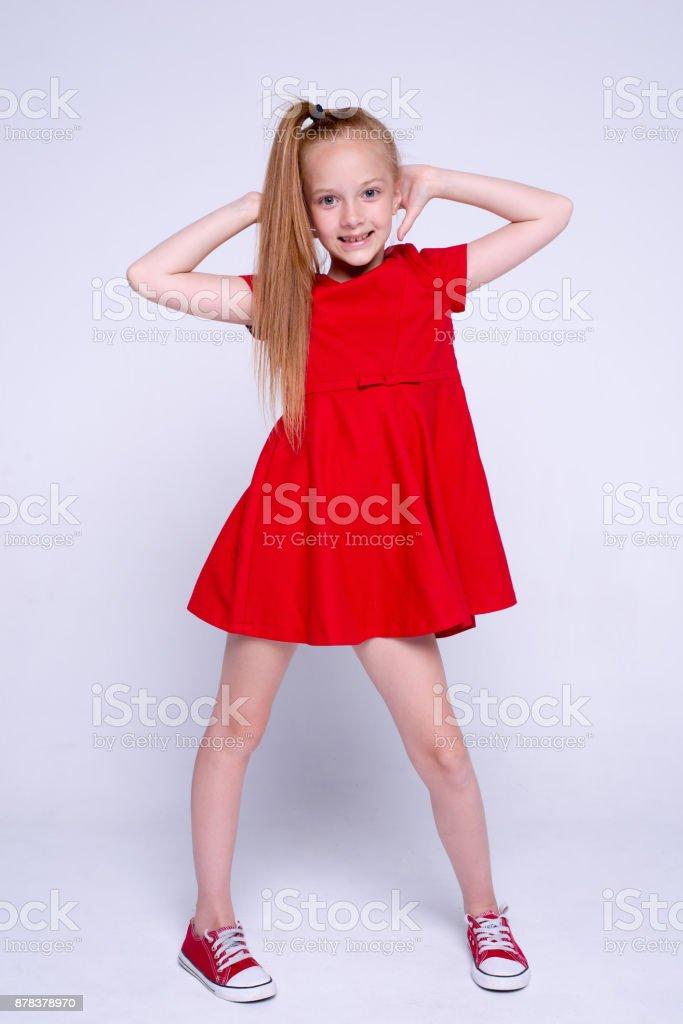 d28d00d408c91 Hermosa pelirroja niña en vestido rojo y zapatillas posando como modelo en  fondo blanco. foto