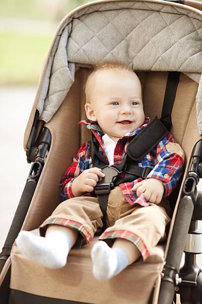 있는 아름다운 작은 웃는 유아용 유모차 거리에서 스톡 사진
