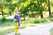 Beautiful little toddler girl playing in park. Adorable child wearing fashion casual clothes and yellow rubber boots.