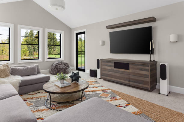 Beautiful living room interior with colorful area rug, large couch, and abundant natural light. Features entertainment console with large screen tv.