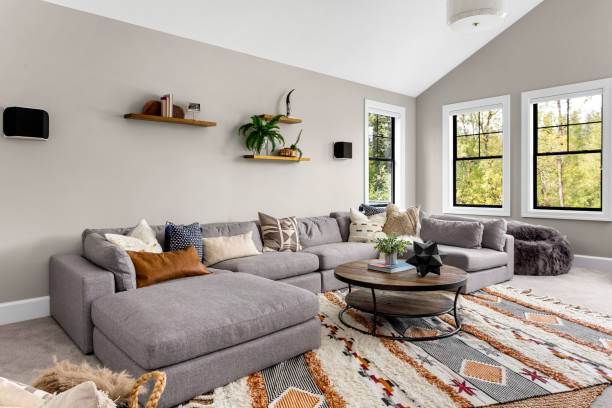 Beautiful living room interior with colorful area rug, large couch, and abundant natural light