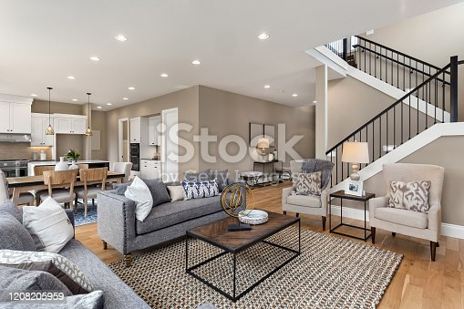 istock Beautiful living room interior with hardwood floors and and view of kitchen in new luxury home 1208205959