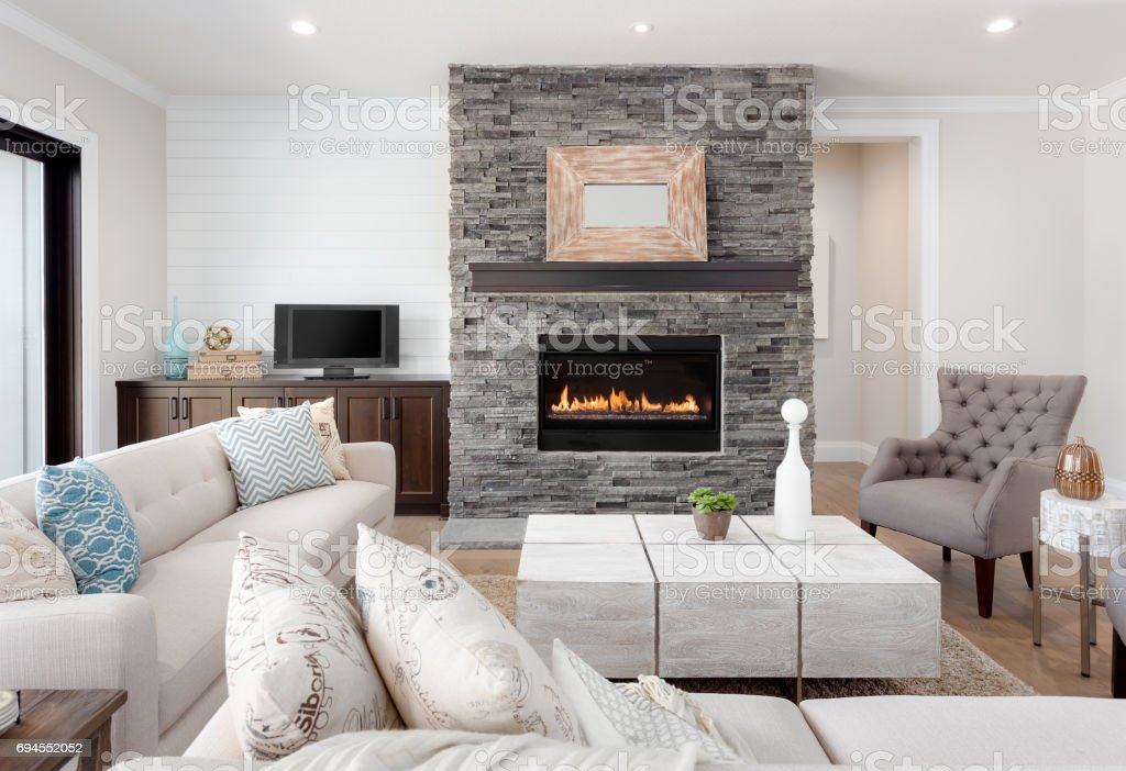 Beautiful living room interior with hardwood floors and fireplace in new luxury home. Couches at Right Angles are Opposite Armchairs and Fireplace with Surround that Stretches to Ceiling stock photo