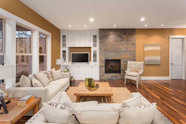 schönes wohnzimmer interieur mit holzböden und kamin im neuen luxus-haus. zwei sofas im rechten winkel und kissen frame gemütliche familienzimmer mit couchtisch und einbauschränke. - wohnschrank stock-fotos und bilder
