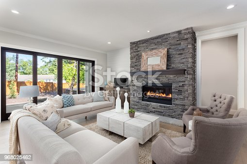istock Beautiful living room interior with hardwood floors and fireplace in new luxury home. 968025462