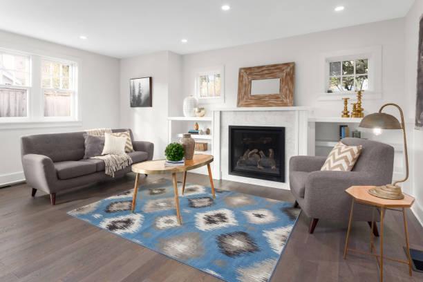 schönes wohnzimmer interieur mit holzböden und kamin im neuen luxus-haus. - kamin wohnzimmer stock-fotos und bilder