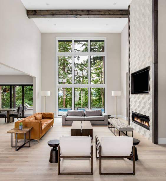 schönes wohnzimmer interieur mit hohen gewölbedecke, dachboden, holzböden und kamin im neuen luxus-haus. hat große bank von windows - große wohnzimmer stock-fotos und bilder