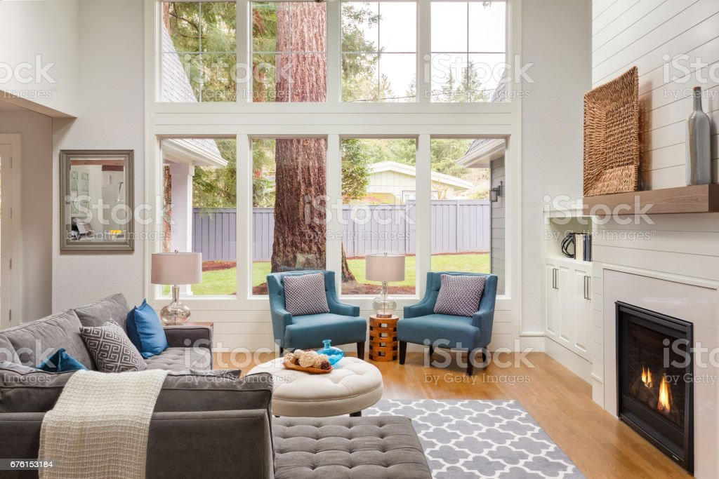 Beautiful living room interior with tall vaulted ceiling, loft area, hardwood floors and fireplace in new luxury home. Has large bank of windows stock photo
