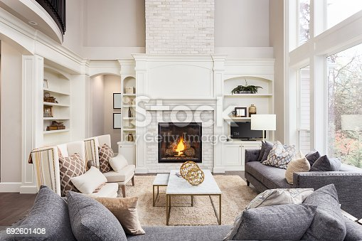 istock Beautiful living room interior with tall vaulted ceiling, loft area, hardwood floors and fireplace in new luxury home. Has large bank of windows 692601408