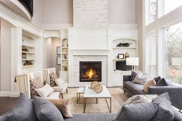 piękne wnętrze salonu z wysokim sklepionym sufitem, obszarem na poddaszu, drewnianymi podłogami i kominkiem w nowym luksusowym domu. posiada duży bank okien - luksus zdjęcia i obrazy z banku zdjęć