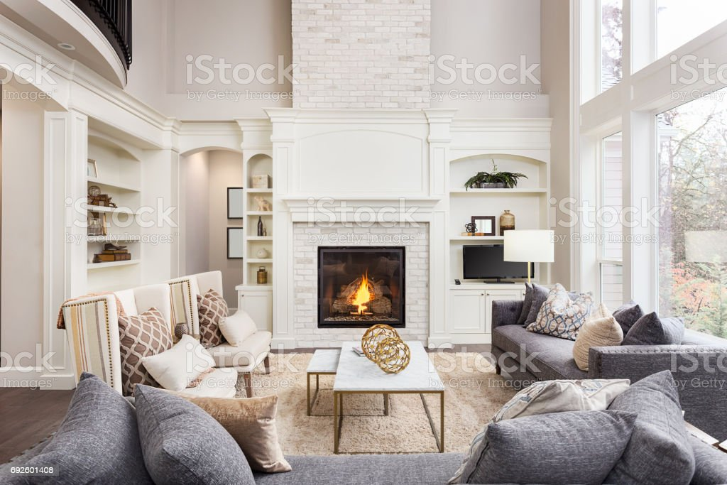 Beautiful living room interior with tall vaulted ceiling loft area hardwood floors and fireplace