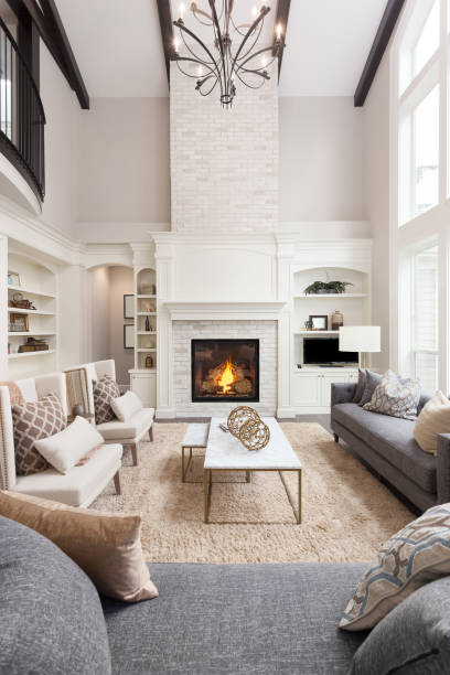 Beautiful living room interior with tall vaulted ceiling, loft area, hardwood floors and fireplace in new luxury home. Has large bank of windows living room in newly constructed luxury home, vertical orientation. model home stock pictures, royalty-free photos & images