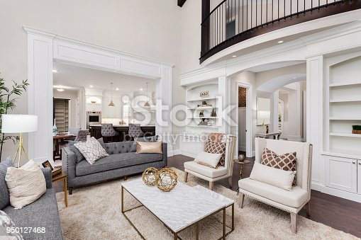 istock Beautiful living room interior with tall vaulted ceiling, loft area, hardwood floors and fireplace in new luxury home. Has view of kitchen and dining area, and loft. 950127468