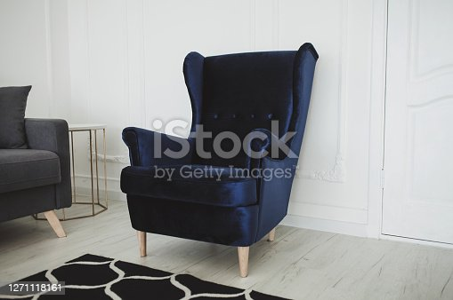 Beautiful living room with blue armchair in modern interior