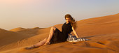 A young woman in a black dress sits on the sand in the desert meeting the sunset