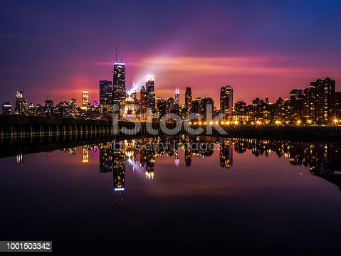 Beautiful long exposure Chicago night skyline photo with building lights at sunset with pink purple and blue clouds in the sky reflecting in a calm pool of water and spotlight shining up into the sky.