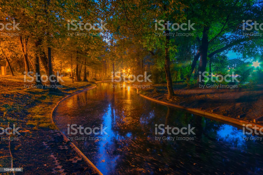 Beautiful long exposure night shot in the park with reflections in the lake stock photo