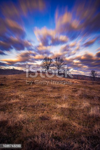 1034754000 istock photo Beautiful long exposure scene with dramatic clouds over some trees with a vibrant blue sky 1035743200