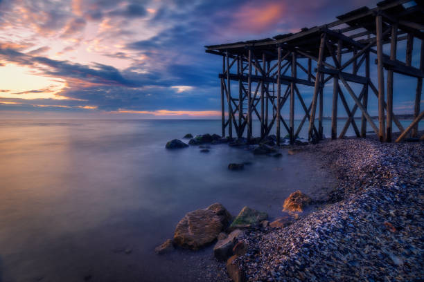 A beautiful long exposure shot of a sunrise or sunset by the Black Sea near a wooden pontoon in Tuzla, Constanta Conty Romania stock photo