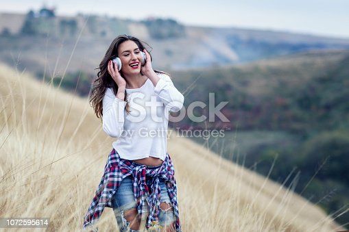 istock Beautiful long hair woman with headphones in the middle of the field with landscape on background 1072595614