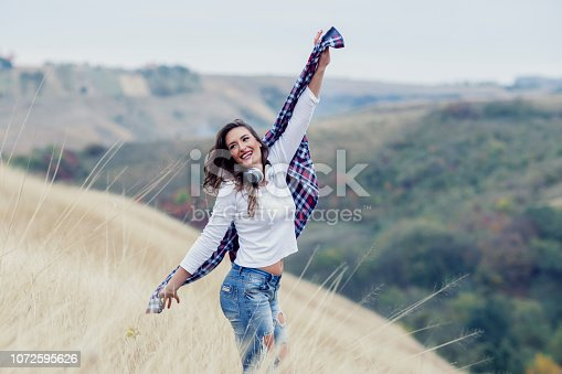 istock Beautiful long hair woman with headphones in the middle of the field with landscape on background 1072595626