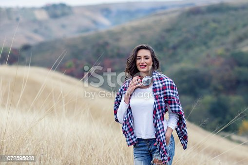 istock Beautiful long hair woman with headphones in the middle of the field with landscape on background 1072595628