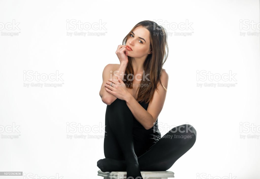 Preciosa morena de pelo largo en medias oscuras se sienta en la silla en el estudio. - foto de stock