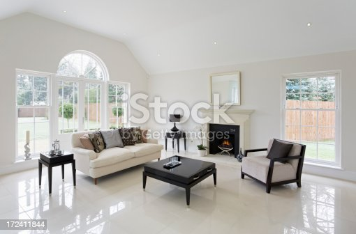 a beautiful cosy lounge in a luxury mansion home with white walls and cream coloured marble floor tiles. A large window area to the left leads out through French doors to a patio and garden. In the centre is a lovely lit fire place with a cradle-style gas appliance with natural looking coals. The furnishing is simple whilst leaving lots of space and a bright setting.