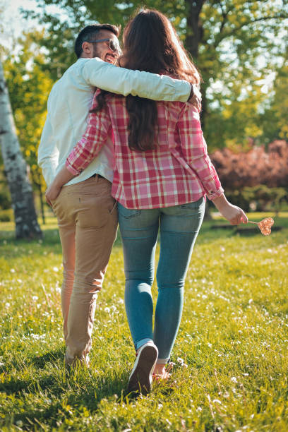 Beautiful love couple on a date walking together in park - foto stock