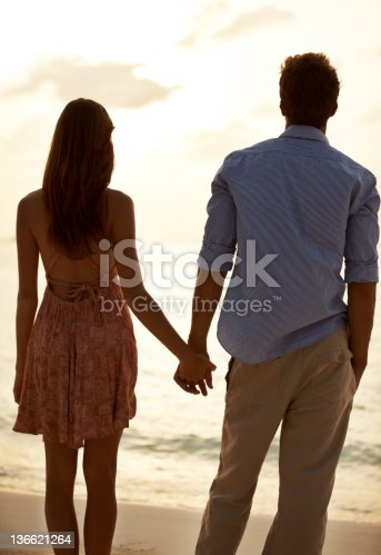 Rear-view image of a young couple holding hands by the seashore against the sunset