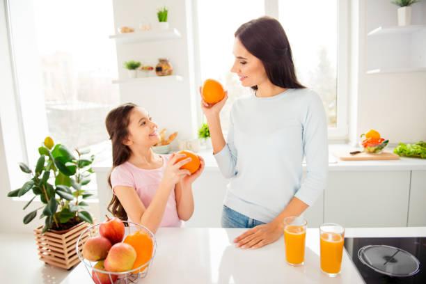 mooie mooie mooie charmante vrolijke moeder en haar kleine beetje - vitamine c stockfoto's en -beelden