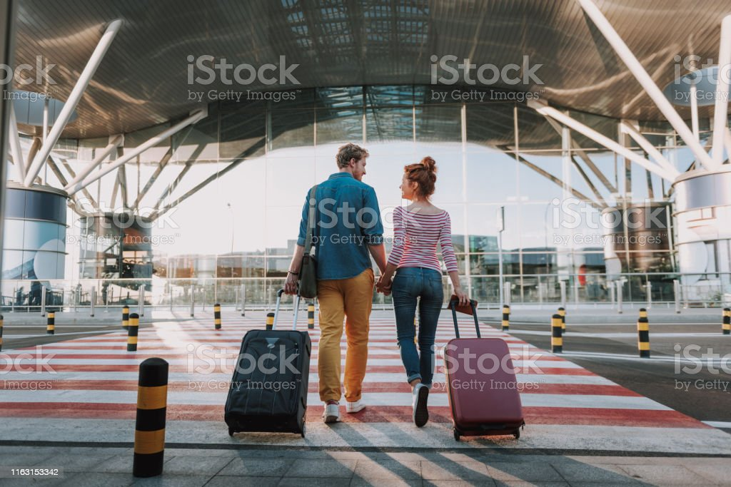 Beautiful loving couple with travel suitcases holding hands in airport Full length back view portrait of young man and his charming girlfriend walking and carrying their trolley bags. They looking at each other and smiling Adult Stock Photo