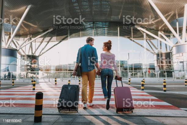 Photo of Beautiful loving couple with travel suitcases holding hands in airport