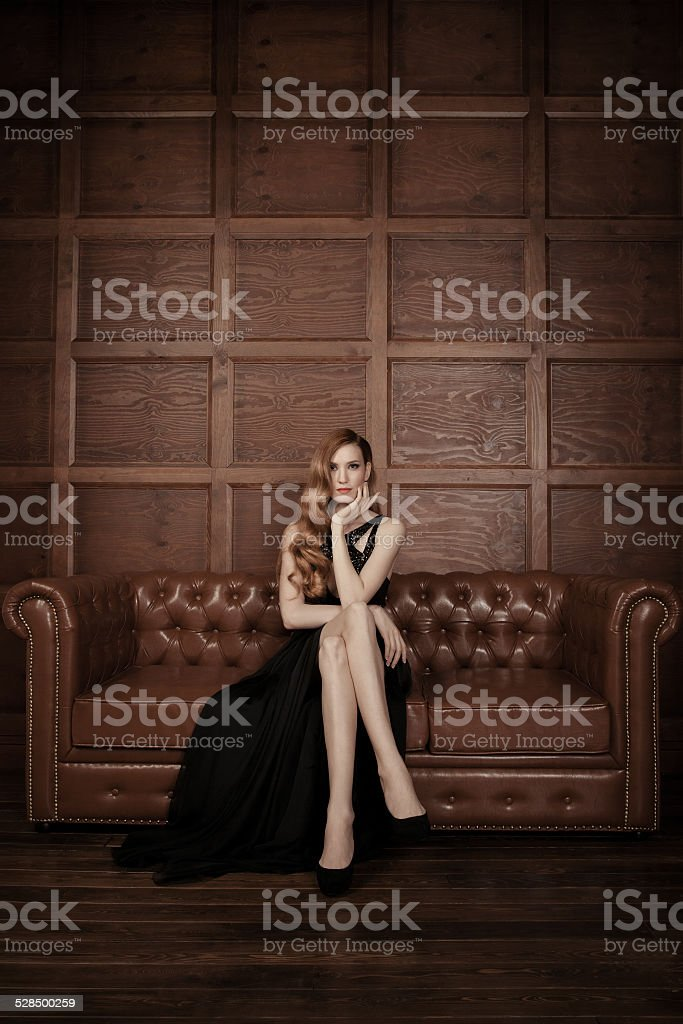 Beautiful luxurious woman sitting on a leather vintage couch. stock photo