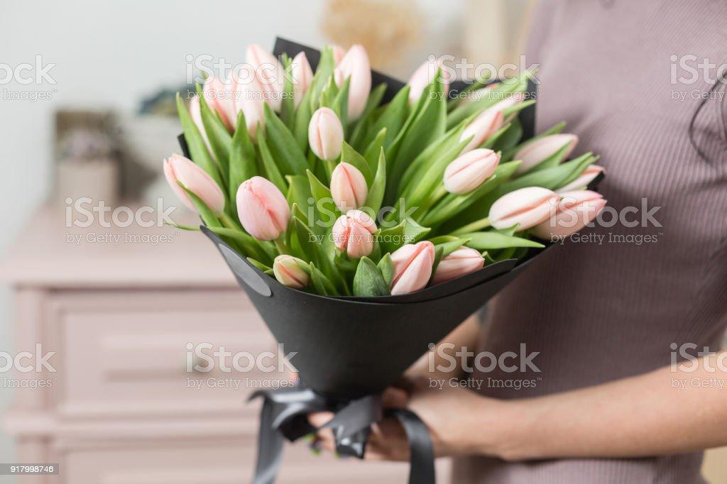 schöne Luxus-Bouquet von rosa Tulpen Blumen in der Hand der Frau. die Arbeit der Floristen in einem Blumenladen. – Foto