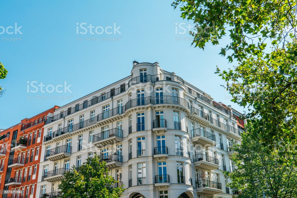 beautiful luxury buildings framed by a green tree stock photo