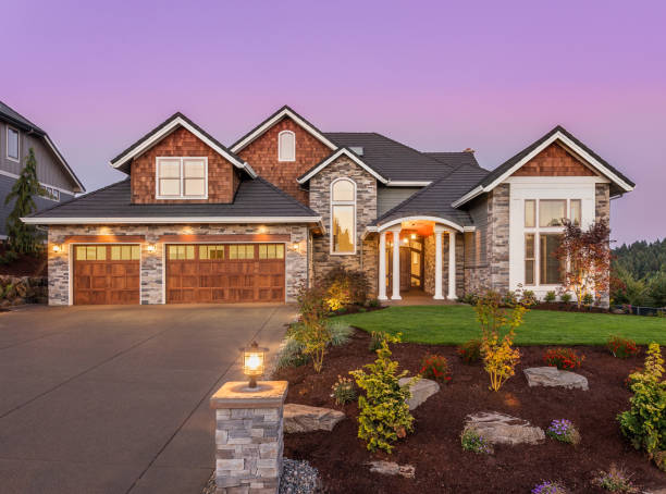 Beautiful luxury home exterior at sunset. Features three car garage and manicured lawn. facade of home with manicured lawn, and backdrop of trees exterior stock pictures, royalty-free photos & images