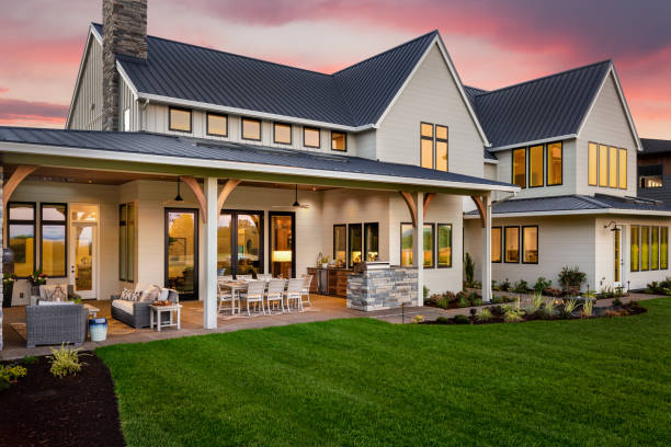 Beautiful luxury home exterior at sunset, featuring large covered patio with outdoor kitchen and barbecue facade of home with manicured lawn and large covered patio house stock pictures, royalty-free photos & images