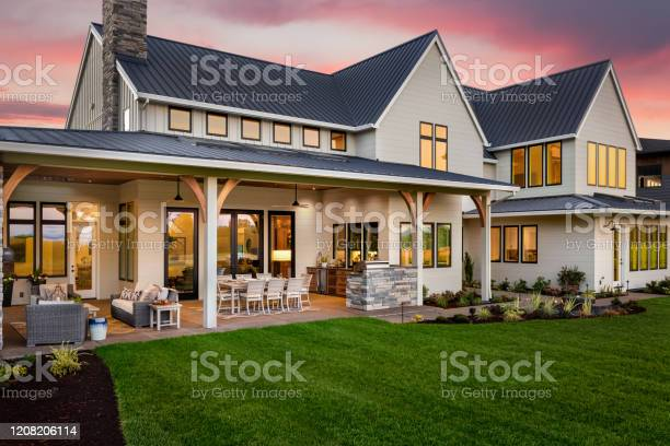 Photo of Beautiful luxury home exterior at sunset, featuring large covered patio with outdoor kitchen and barbecue