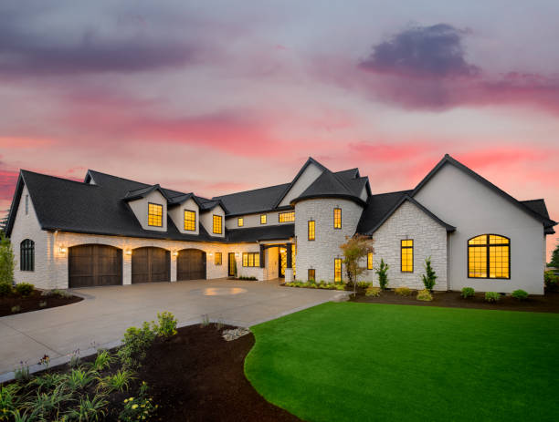 Beautiful luxury home exterior at sunset facade of home with manicured lawn, and backdrop of trees and dark blue sky grounds stock pictures, royalty-free photos & images
