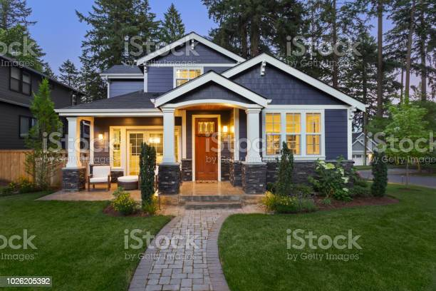 facade of home with manicured lawn, landscaping, and backdrop of trees and dark blue sky. Glowing interior lights create a welcoming mood.