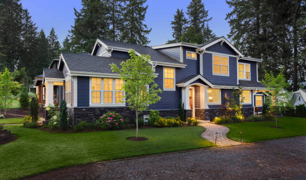 Beautiful luxury home exterior at twilight facade of home with manicured lawn, landscaping, and backdrop of trees and dark blue sky. Glowing interior lights create a welcoming mood. model home stock pictures, royalty-free photos & images