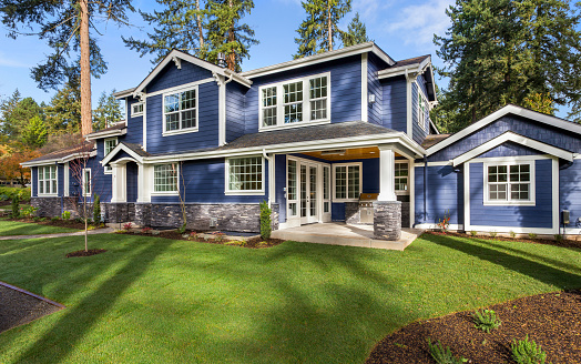 istock Beautiful luxury home exterior on bright sunny day with green grass and blue sky 968025444